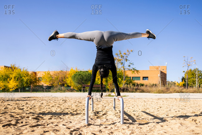 Back view of fit female athlete performing handstand with splits on parallel bars while doing exercises during calisthenics training