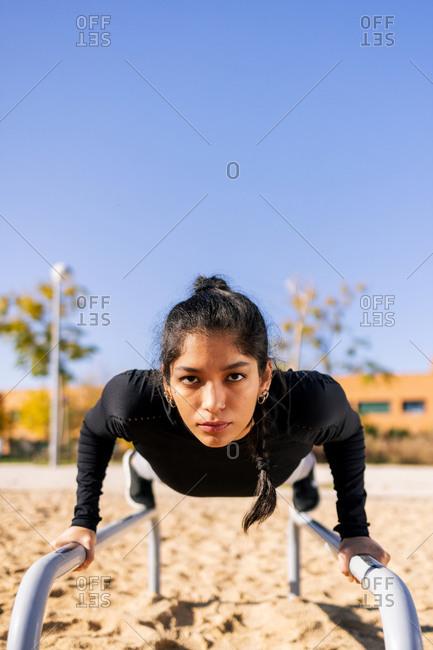 Focused ethnic female athlete doing exercises on parallel bars during calisthenics workout