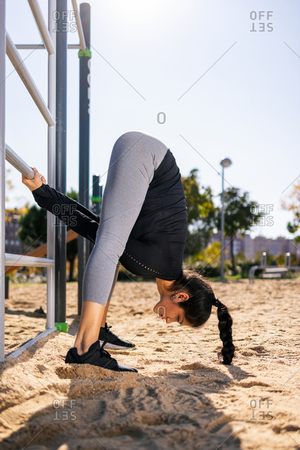Side view of flexible athletic female doing exercises near bars while stretching body during calisthenics training