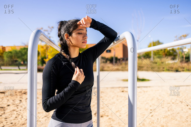 Exhausted ethnic female athlete standing near parallel bars on sports ground while leaning on hand and having break during active training on summer day