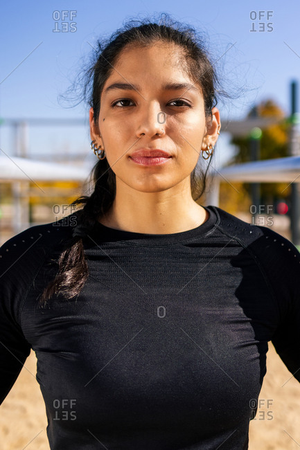 Fit ethnic sportswoman in activewear standing on sports ground and confidently looking at camera