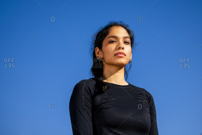 Fit ethnic sportswoman in activewear standing on sports ground and confidently looking at camera with clear blue sky on the background