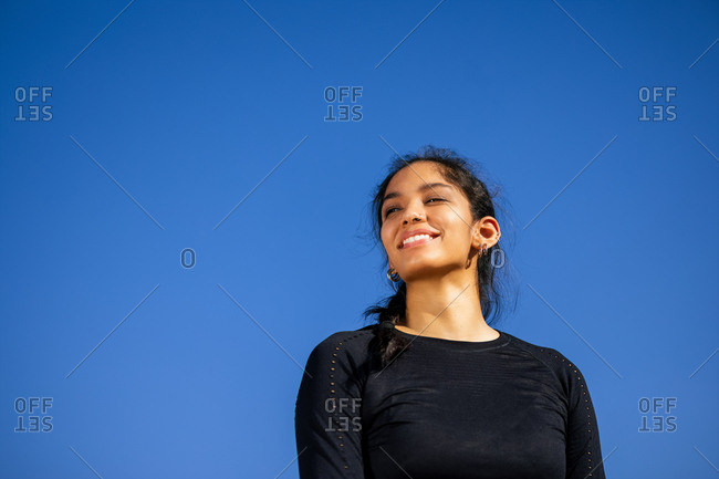 Fit ethnic happy sportswoman in activewear standing on sports ground and confidently looking away with clear blue sky on the background