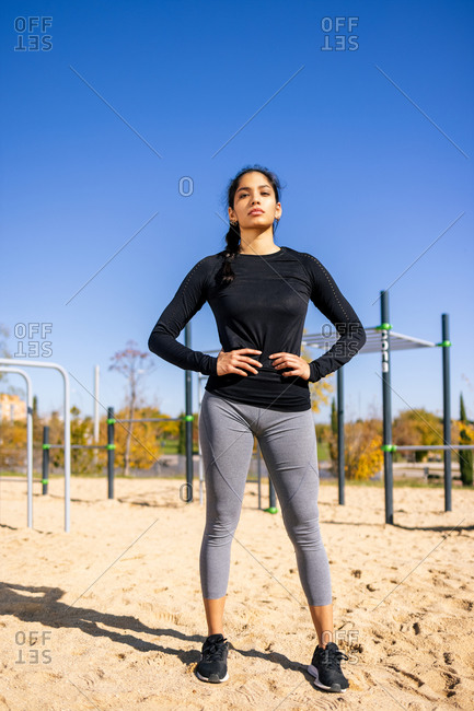 Fit ethnic sportswoman in activewear standing with hands on waist on sports ground and confidently looking at camera