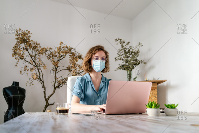 Concentrated young female entrepreneur in casual clothes and medical mask typing on laptop while working on project during quarantine