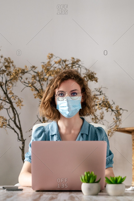 Concentrated young female entrepreneur in casual clothes and medical mask typing on laptop while working on project during quarantine. Looking at camera