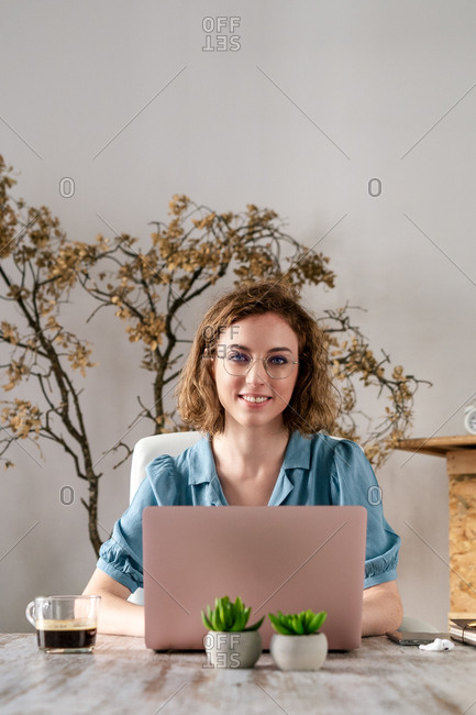 Young female freelancer with wavy hair in casual clothes and eyeglasses working remotely on laptop looking at camera