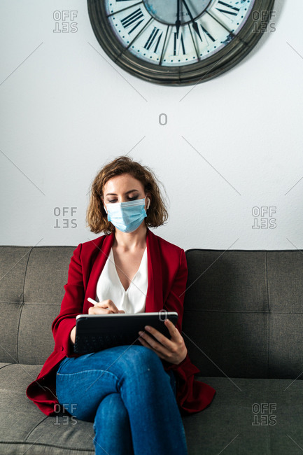 Unrecognizable young lady in stylish outfit and face mask using table while sitting on comfortable couch while working remotely from home during quarantine