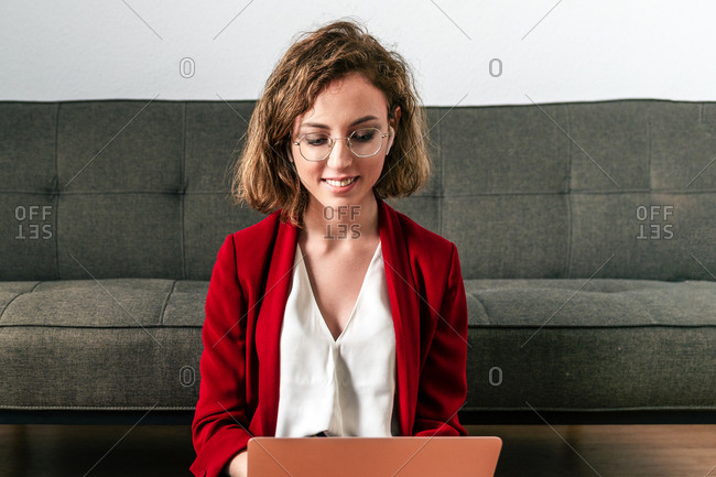 Cheerful young female in stylish outfit and true wireless earphones smiling while having video call via tablet during remote work at home