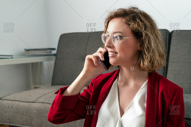 Happy young businesswoman in classy outfit and eyeglasses smiling and looking away while having phone conversation on smartphone in modern office
