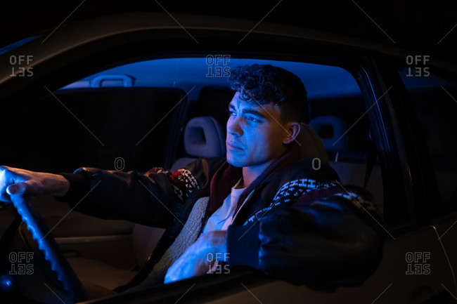 Side view of confident young male millennial sitting in modern car with blue neon illumination at night and looking away