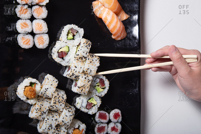 Top view of crop unrecognizable person with chopsticks eating various delicious rolls and sushi placed on black plate