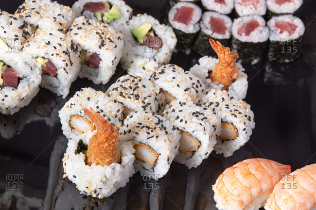 Various delicious rolls and sushi placed on black plate