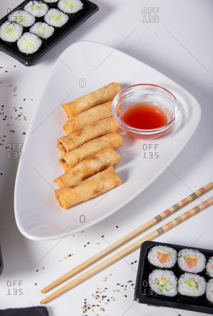 High angle of tasty spring rolls with ketchup in bowl placed on table with various sushi in Asian restaurant