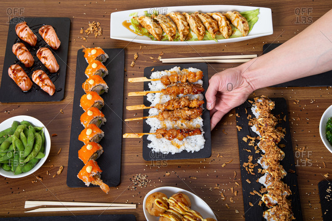 Top view of unrecognizable person with assorted sushi and rolls arranged on wooden table in restaurant with Asian food