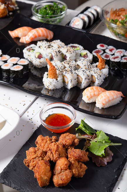 Various sushi and rolls placed on table in Asian restaurant