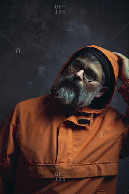 Pensive stylish tattooed adult ethnic male with gray beard in trendy hooded jacket and eyeglasses looking away against black background