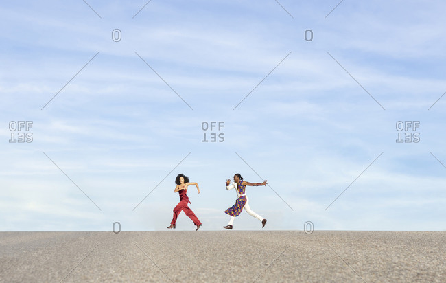 Side view of active African American couple in fancy outfit running along dry hill on background of blue sky on sunny day