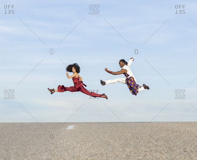 Side view of African American couple in trendy traditional clothes jumping high above asphalt road and performing dance on background of blue sky