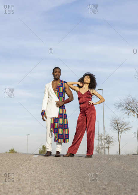 African American couple wearing fancy clothes standing together on the road on background of blue sky on sunny day