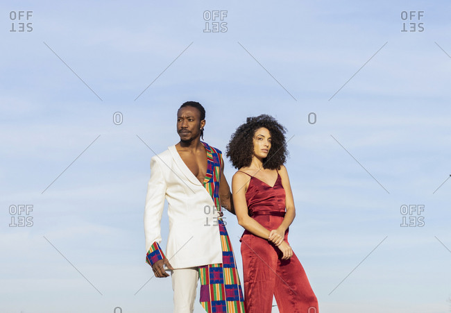 African American couple wearing fancy clothes standing together on background of blue sky on sunny day