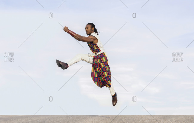 Side view of African American male dancer in trendy outfit jumping above road while performing energetic movements against blue sky looking away