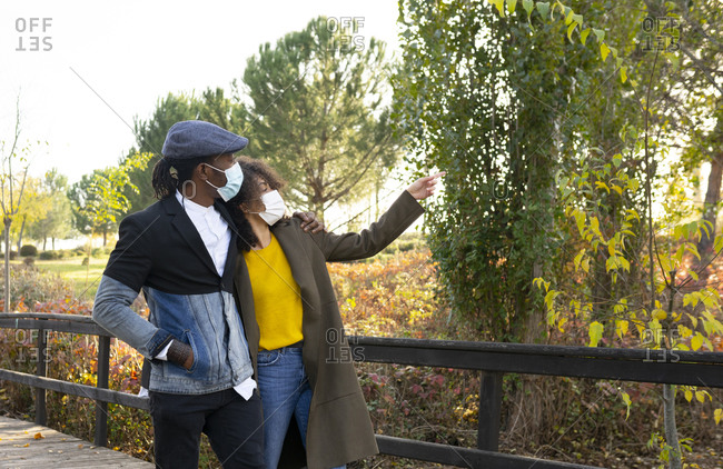 Stylish African American couple in medical masks hugging and walking in autumn park during coronavirus epidemic
