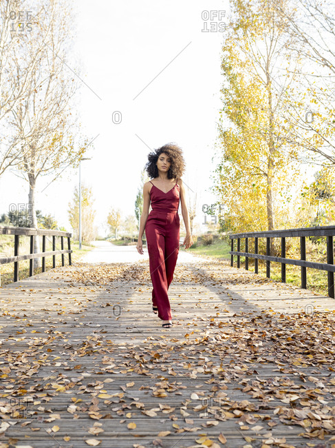African American female with Afro hairstyle and in trendy silk overalls walking along wooden path in park and looking at camera