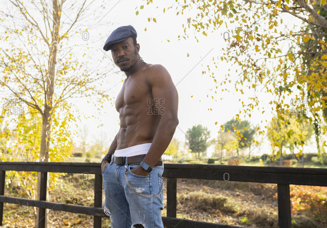 Confident African American male in jeans and with muscular naked torso standing with hands in pockets in park and looking at camera