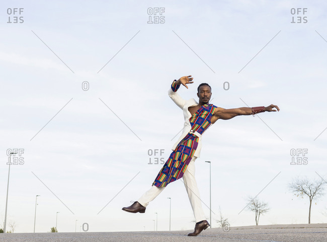 Side view of African American male dancer in trendy outfit performing energetic movements against blue sky