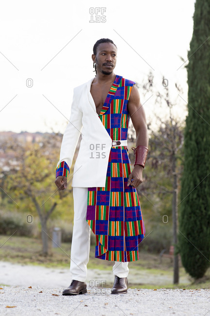 Determined African American male model in traditional costume walking on background of blue cloudy sky and looking away