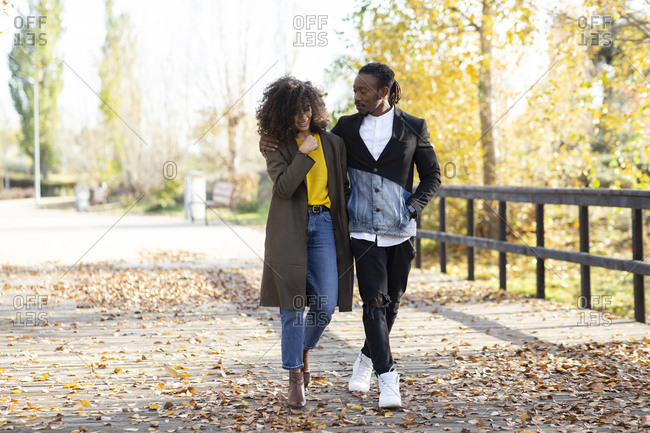 Side view of African American couple in trendy outfit walking along wooden path in park and enjoying stroll in fall