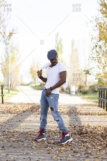 Handsome black male in trendy casual clothes standing in autumn park and looking away