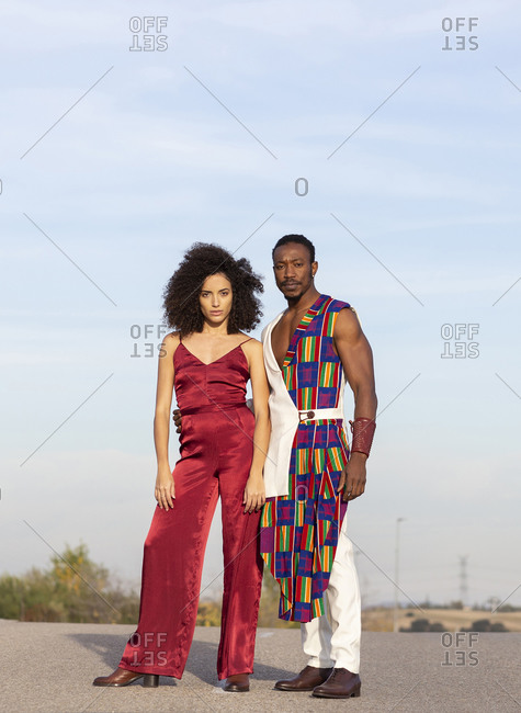 African American couple wearing fancy clothes standing together on the road on background of blue sky on sunny day looking at camera