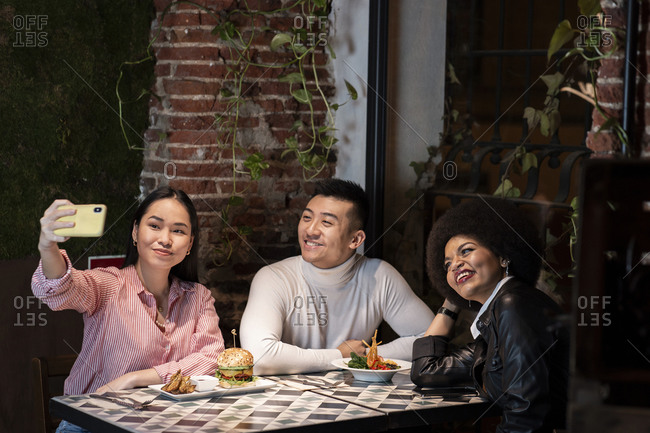 Group of positive young multiracial friends having fun and taking selfie on smartphone while enjoying delicious meal together in cozy cafe