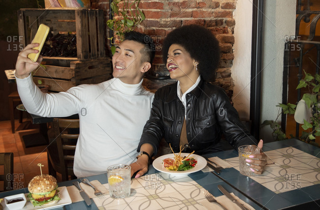 Happy young Asian man and African American girlfriend having fun and taking selfie on smartphone during lunch in restaurant