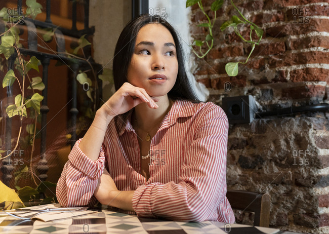 Young tranquil Asian female looking away in casual clothes sitting alone at table in cafe and waiting for order