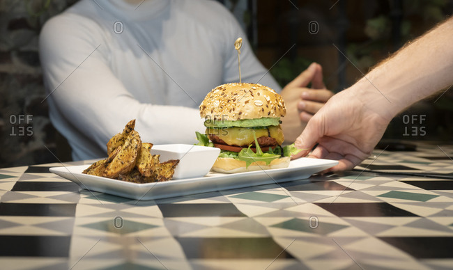 Crop anonymous waiter holding tray with delicious appetizing burger served with baked potatoes and sauce while serving meal for clients in cafe
