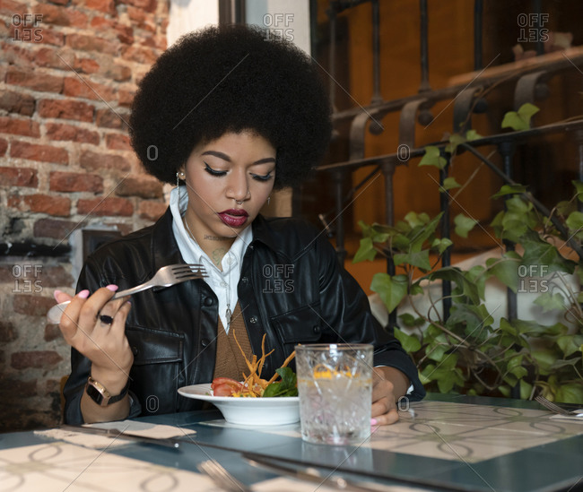 African American female with curly hair having dinner with portion of delicious salad and glass of drink at table in cozy restaurant