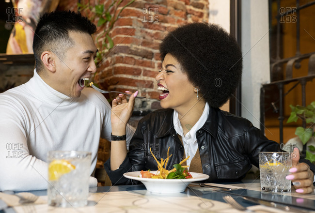 Laughing African American young woman feeding cheerful Asian boyfriend with salad while having fun during lunch in cafe