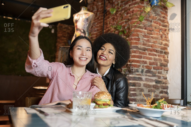 Playful young diverse female friends sitting at table with various dishes and taking selfie on smartphone with funny faces while having dinner together in restaurant