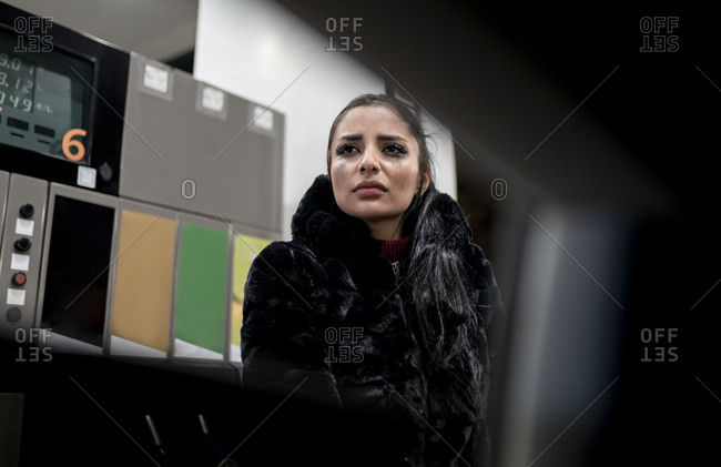 Through window view of unhappy young female with smeared makeup on face having problem and crying while standing near car