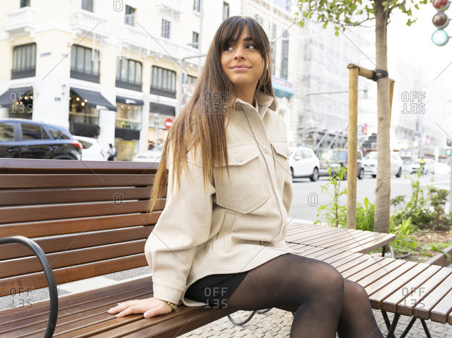 Side view of positive young ethnic lady with long dark hair in trendy outfit relaxing on wooden bench and looking away in Madrid