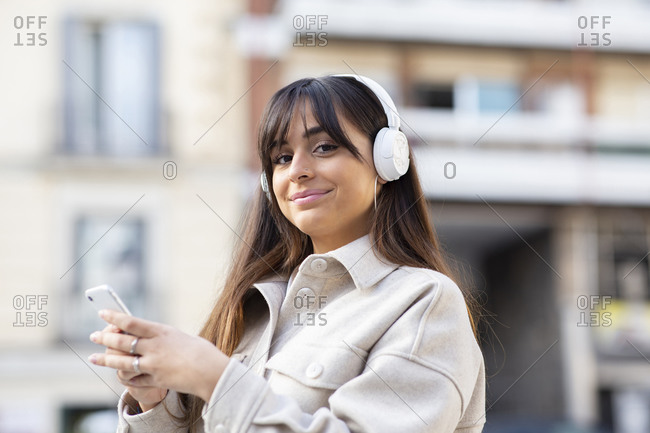 Positive young ethnic female millennial with long dark hair in stylish clothes listening to music in headphones and smiling while taking selfie on smartphone in city