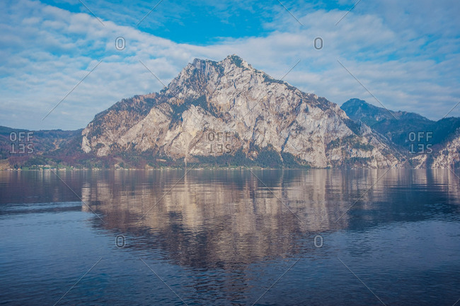 Picturesque landscape of massive rocky mountain reflecting in water of lake against cloudy blue sky in Hallstatt