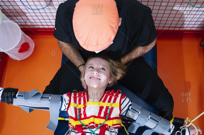 Crop anonymous specialist giving support to girl with Angelman syndrome during rehabilitation training with elastic straps