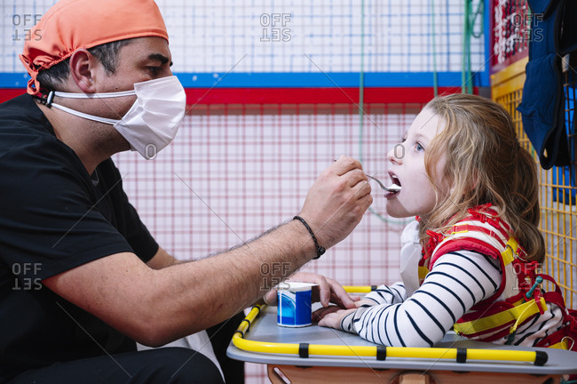 Side view of male specialist in medical mask giving yogurt to disable little girl wit Angelman syndrome while having break during developing activities