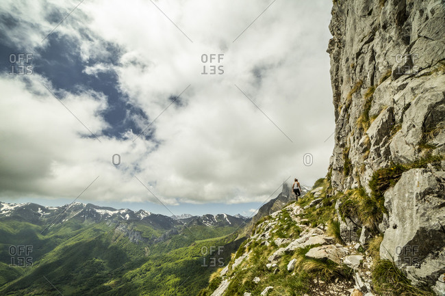 Unrecognizable female hiker in activewear exploring nature in spectacular rocky mountainous valley covered with green grass in Fuente De