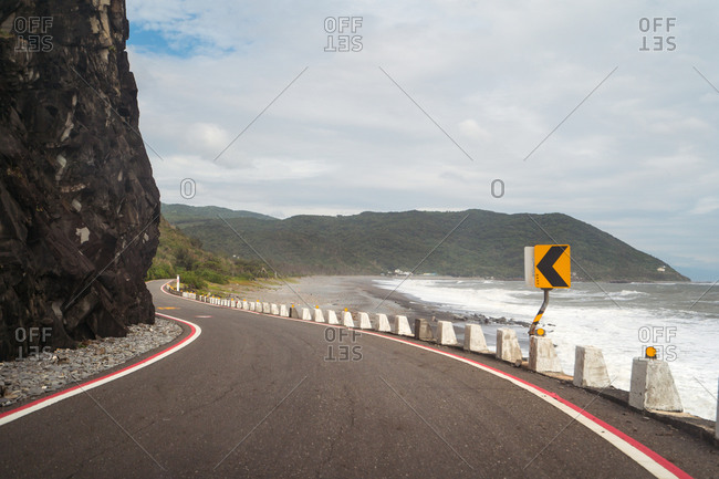 Amazing view of empty asphalt roadway surrounded by waving sea and picturesque mountains on sunny day on East Coast