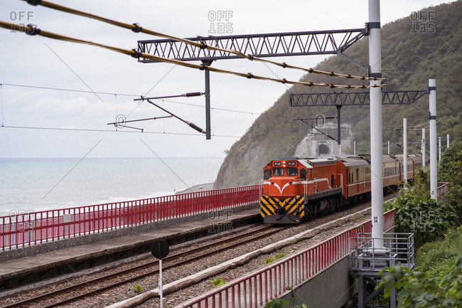 Scenic view of train riding along railway located on bridge in mountains on East Coast